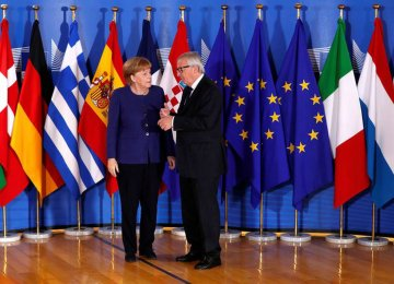 German Chancellor Angela Merkel is welcomed by European Commission President Jean-Claude Juncker at the start of an emergency European Union leaders' summit on immigration at the EU Commission headquarters in Brussels on June 24.