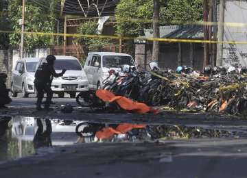 Members of police bomb squad inspect wreckage of motorcycles at the site where an explosion went off outside a church in Surabaya, East Java, Indonesia on May 13.