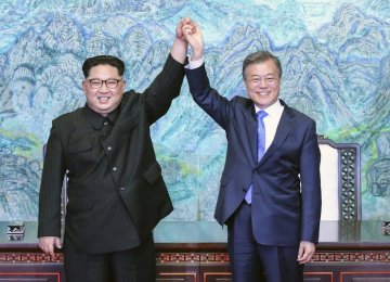 North Korean leader Kim Jong-un (L) and South Korean President Moon Jae-in hold hands at the border village  of Panmunjom in the Demilitarized Zone, South Korea, on April 27.