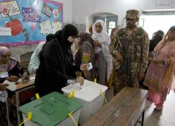 A woman casts her vote at a polling station for the parliamentary elections in Rawalpindi, Pakistan, on July 25.