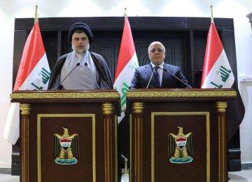 Iraqi Shia cleric Muqtada al-Sadr (L) speaks during a news conference with Iraqi Prime Minister Haider al-Abadi in Baghdad, Iraq on May 19.