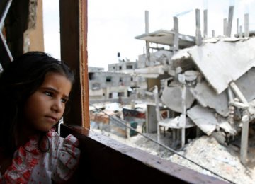 A Palestinian girl inside her family's partially destroyed home looks at the destruction outside in the Shejaiya neighborhood of Gaza City. (File Photo)