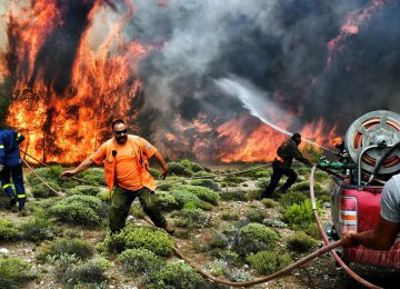 Firefighters and volunteers try to extinguish flames during a wildfire at the village  of Kineta, near Athens, on July 24.