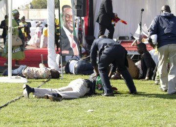 Injured people lay on the ground following an explosion at a ZANU-PF rally in Bulawayo on June 23.