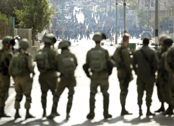 Israeli forces keep watch as Palestinian protesters throw stones and shout slogans near an Israeli checkpoint in the West Bank city of Bethlehem on December 7.