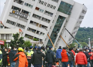 Support girders help prop up a building that came off its foundation, the morning after a 6.4 magnitude quake hit the eastern Taiwanese city of Hualien.