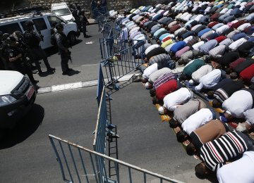 Muslim worshippers pray perform the traditional Friday prayers on a street outside the Lion Gate as Israeli police blocks the access to Al-Aqsa Mosque on July 14.