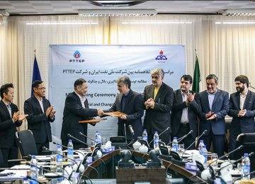 PTTEP Executive Vice President Prapat Soponpongpipat (3rd L) shakes hand with the NIOC deputy Gholamreza Manouchehri (4th L) in Tehran on Dec. 6.