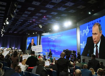 Video screens display President Vladimir Putin speaking during his annual press conference in Moscow while journalists hold the name of their media, on December 23.