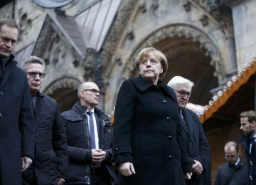 Chancellor Angela Merkel observes a minute's silence at the scene of the carnage in Berlin.