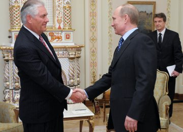 Vladimir Putin (R) shakes hands with Rex Tillerson at a meeting in April 2012. (File Photo)