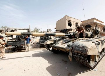 A fighter from Libyan forces allied with the UN-backed government sits atop a tank after capturing new areas from IS terrorists in Sirte, Libya, on Oct. 14.