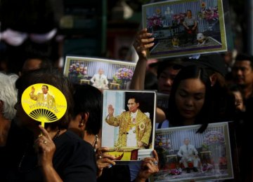 Mourners hold up pictures of Thailand's late King Bhumibol Adulyadej as they wait  in line to offer condolences at the Grand Palace in Bangkok, Thailand, on Oct. 15.