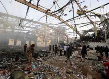 People inspect the aftermath of a Saudi-led coalition airstrike in Sana'a, Yemen, on Oct. 8.