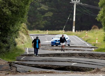 Local residents look at damage caused by an earthquake along State Highway One near the town of Ward, south of Blenheim on New Zealand's South Island on Nov. 14.