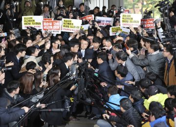 Choi Soon-sil (C), who is involved in a political scandal, reacts as she is surrounded by media and protesters upon her arrival at a prosecutor's office in Seoul, South Korea, on Oct 31.