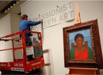A man hangs a sign at Sotheby's auction house in New York as Frida Kahlo's 1929 self-portrait 'Girl with Necklace' sits on an easel.