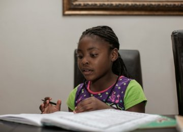 Seven-year-old author Michelle Nkamankeng does her homework at her house in Johannesburg.