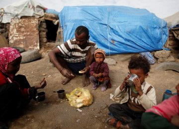 A family eats breakfast outside their hut at a camp for people displaced by the war near Sana'a on Sept. 26, 2016. (File Photo)