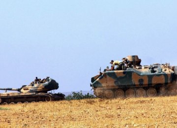 A Turkish Army tank and an armored vehicle are stationed near the border with Syria, in Karkamis, Turkey, Aug. 23.
