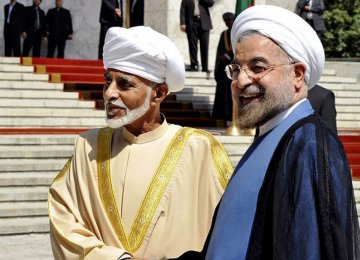President Hassan Rouhani (R) greets Oman's Sultan Qaboos bin Said at the presidential palace in Tehran on August 25, 2013.