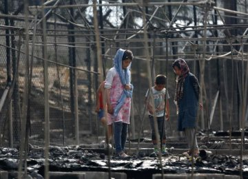 Migrants stand among the remains of a burned tent at the Moria migrant camp,  on the island of Lesbos, Greece, on Sept. 20.