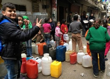 Children with cans line up for water in Nubel, north of Aleppo. (File Photo)