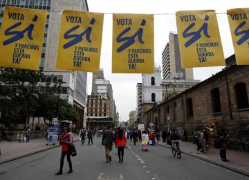 Pedestrians walk under a banner supporting Colombian plebiscite in downtown in Bogota, Colombia, on Sept. 29.