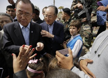 WB President Jim Yong Kim (C), accompanied UN Secretary-General Ban Ki-moon at an informal Syrian refugee camp in Tripoli, Lebanon, in March. Kim says he wants to turn the World Bank into a more agile and efficient banking group.