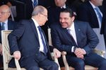 Saad al-Hariri (R) talks with President Michel Aoun while attending a military parade to celebrate  the 74th anniversary of Lebanon's independence in Beirut, Nov. 22.