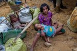 A Rohingya girl, who spent four days in the open after crossing over from Myanmar into Bangladesh, holds her sister at Kutupalong refugee camp, Bangladesh on Oct. 19.
