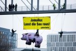 "A banner from Greenpeace reads ""Jamaica, let the pig out"" —urging the ""Jamaica coalition"" to reach a conclusion."