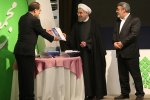 President Hassan Rouhani receives the atlas from Health Minister Hassan Hashemi (L) as Interior Minister Abdolreza Rahmani-Fazli (R) looks on.