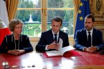President Emmanuel Macron (C) signs a set of executive orders making sweeping changes to France's complex labor laws on Friday.