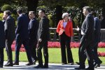 British Prime Minister Theresa May looks to passing  by heads of government after the family photo at the informal EU summit in Salzburg, Austria, Sept. 20.