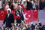 Turkey's President Recep Tayyip Erdogan (R) accompanied by his wife Emine throws flowers to his supporters as he arrives to deliver a speech at his ruling Justice and Development Party congress in Ankara, Turkey, on August 18.