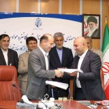 Head of Sistan-Baluchestan's Ports and Maritime Organization Behrouz Aghaei (L) shakes hands with Managing Director of Life Trade Promotion Company Mohammad Arazesh after signing the agreement on May 23.