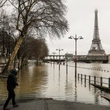 A man stands by the flooded banks of the river Seine in Paris on January 23, near the Eiffel tower as the Seine level has risen to a height of 4.57 metres, several metres higher than its normal level.