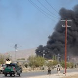 Smoke rises from police headquarters while Afghan security forces keep watch after a suicide car bomber and gunmen attacked the provincial police headquarters in Gardez, the capital of Paktia Province, Afghanistan on October 17.