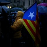 A demonstrator holds an Estelada (Catalan separatist flag) during a gathering in front of the Spanish Central Government headquarters in Barcelona on October 19.