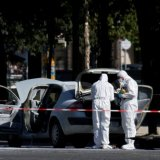 Police officers inspect a burned car on the Champs-Elysees Avenue in Paris, France, on June 19.