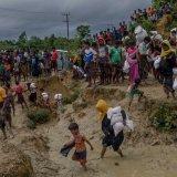 A crowd of Rohingya walk carrying aid through  a muddy refugee camp.