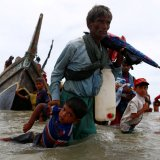 A Rohingya refugee man pulls a child as they walk to the shore after crossing the Bangladesh-Myanmar border  by boat through the Bay of Bengal in Shah Porir Dwip, Bangladesh on September 10.
