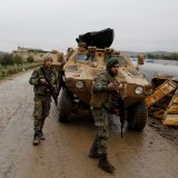 Members of Turkey-backed Free Syrian Army police forces secure the road as they escort a convoy near Azaz, Syria, on Jan. 26.