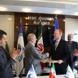 CEO of Iran Aseman Airlines Hossein Alayi (L) shakes hands with James Larson, regional director for contracts at Boeing, in Tehran on March 18.