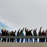 """Young people wave colored flags reading """"Peace"""" as they form a symbolic human wall."""