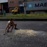 A youth moves quickly to collect grains of corn  on the street that fell from a truck that was looted outside the port in Puerto Cabello.