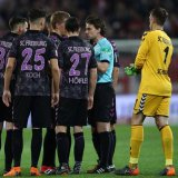 Referee Guido Winkmann is confronted by the Freiburg squad after ordering the players back onto the pitch.