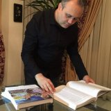 Ramin Hajian Fard turning the pages of  the encyclopedia