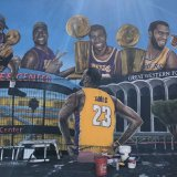 The mural in LA shows LeBron James looking up at several Lakers stars and  its historic venues.